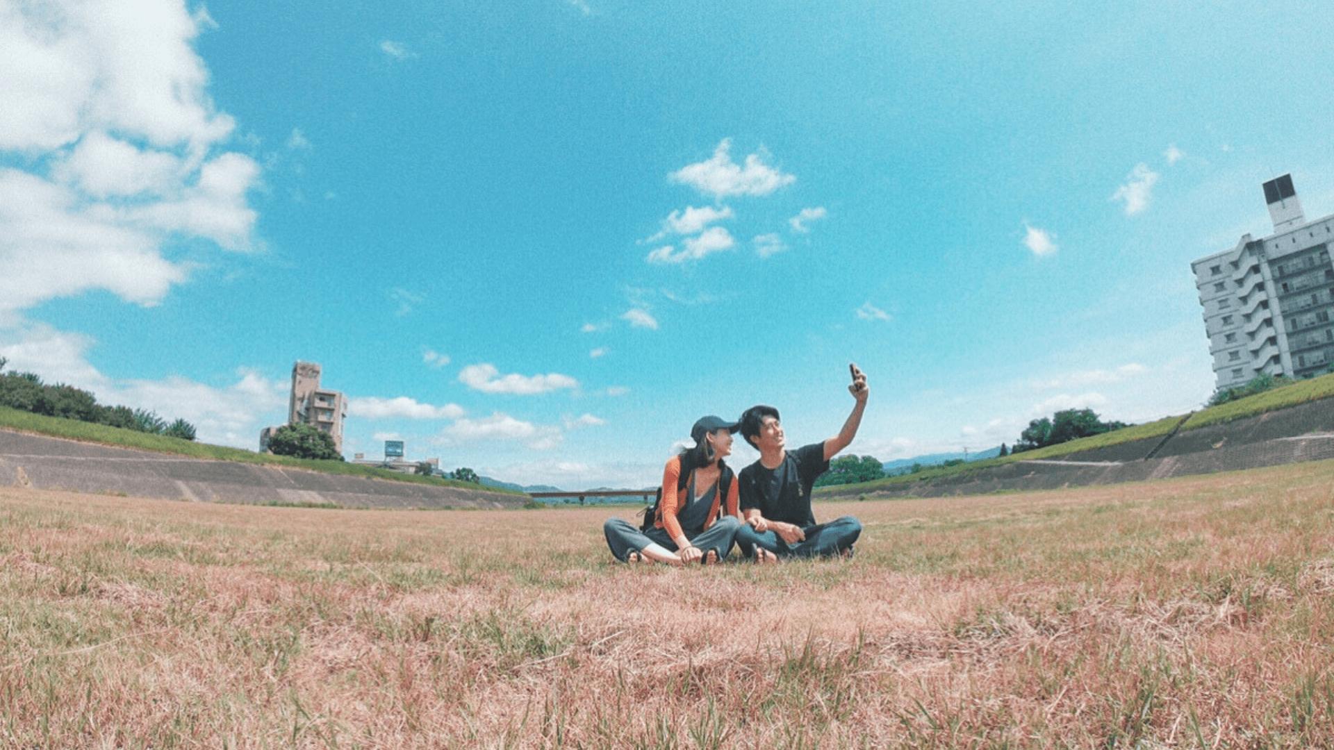芝生の上で自撮り写真を撮るカップル